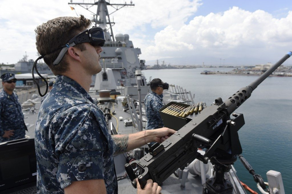U.S. Navy using VR and AR - Sailor defending against virtual enemy combatants during a virtual reality training program demonstration.