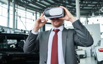 Man wearing classical suit standing at modern car showroom and using VR headset while testing new automobile