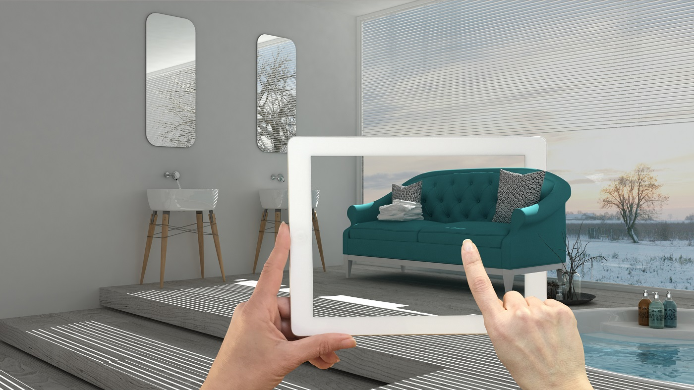 Augmented reality concept. Hand holding tablet with AR application used to simulate furniture and interior design products in real home